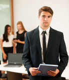 Young Business man   standing in first plain with coworkers in b Stock Photo