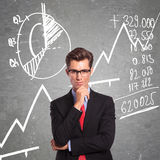 Man in front of charts. Young business man standing in front of some graphs and charts with a pensive look on his face royalty free stock photo