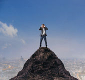 Young business man standing on top of mountain and spying by bin Royalty Free Stock Photos