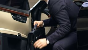 Young business man in suit with briefcase getting out of expensive black car. Stock footage stock video footage