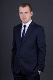 Young business man in suit over grey Stock Photos