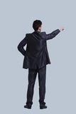 Young business man in a suit pointing with his finger. Isolted on gray Royalty Free Stock Photos