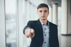 Young business man in a suit pointing with his finger office Royalty Free Stock Photography
