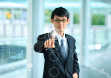 Young business man in a suit pointing with his finger to touch s. Creen interface Royalty Free Stock Image