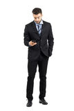 Young business man in suit reading message on his cellphone. Royalty Free Stock Images