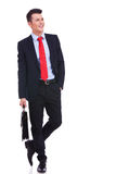 Young business man with suitcase looking to side. Young business man with suitcase standing with his hand in pocket and looking to a side on white background Royalty Free Stock Image