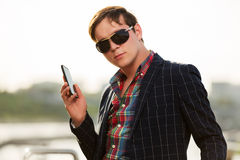 Young business man in sunglasses with a mobile phone Royalty Free Stock Image