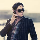 Young business man in sunglasses using smart phone on city street royalty free stock images