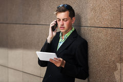 Young business man with tablet computer calling on phone Royalty Free Stock Photos
