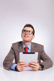Young business man with tablet looks up and smiles Stock Images