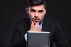 Young business man with tablet looks at you pensively Stock Images
