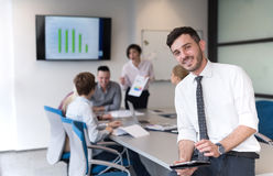 Young business man with tablet at office meeting room. Portrait of happy young businessman with tablet computer office. People group on team meeting in Stock Image