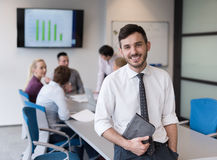 Young business man with tablet at office meeting room. Portrait of happy young businessman with tablet computer office. People group on team meeting in Royalty Free Stock Photo