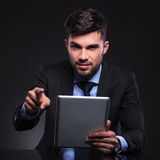 Young business man with tablet points at camera Royalty Free Stock Photography
