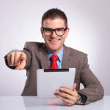 Young business man with tablet points at you and smiles Royalty Free Stock Images