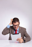 Young business man with tablet scratches his head Stock Image