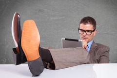 Young business man with tablet sits with feet on desk Stock Photos