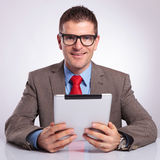 Young business man with tablet smiles for you Royalty Free Stock Photography