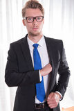 Young business man taking something out of his pocket Royalty Free Stock Photo