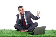 Young business man talking. Young business man barefoot siting on a green carpet with lap top in front of him talking on a mobile phone Royalty Free Stock Photos