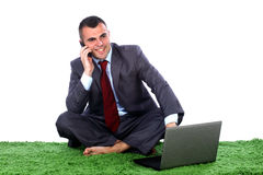 Young business man talking. Young business man barefoot siting on a green carpet with lap top in front of him talking on a mobile phone Royalty Free Stock Image
