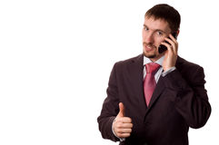 Young business man talking on cell phone. Young modern business man talking on cell phone, with thumbs up (isolated on white royalty free stock photo