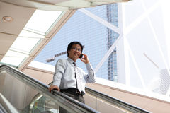 Young business man talking on cell phone. At modern office, asian male Stock Photo