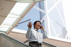 Young business man talking on cell phone. At modern office, asian male Stock Images