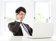 Young business man talking happily by smart phone in office Royalty Free Stock Photography