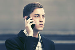 Young business man talking on mobile phone in city street Stock Image