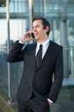 Young business man talking on mobile phone outdoors Stock Images