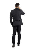 Young business man talking on the phone walking away rear view. Full body length portrait isolated over white studio background royalty free stock photo