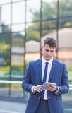 Young business man think look up hold tablet pc Royalty Free Stock Images