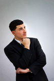 Young business man thinking in black suit Stock Image
