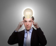 Young business man thinking with light bulb Royalty Free Stock Photos