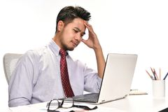 Young business man thinking while working with laptop Royalty Free Stock Photos