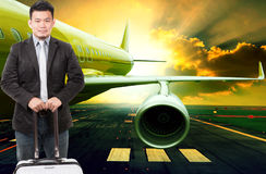 Young business man and traveling luggage standing in front of pa Royalty Free Stock Images