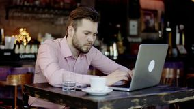 Young business man is typing on a laptop. Sitting in a bar stock video