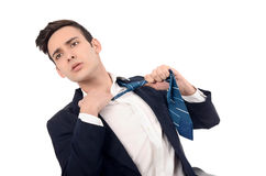 Young business man undressing his suit, pulling his tie. Stock Photos