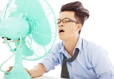 Young business man use fans to cool down. Summer heat Royalty Free Stock Photos