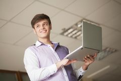 Young business man using laptop while standing at the office Stock Images