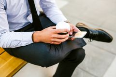 Young Business Man Using Smartphone While Drinks Coffee To Go. And Sitting On Bench Stock Photo