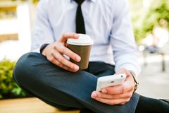 Young Business Man Using Smartphone While Drinks Coffee To Go. And Sitting On Bench Stock Images