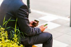 Young Business Man Using Smartphone While Drinks Coffee To Go. And Sitting On Bench Royalty Free Stock Images