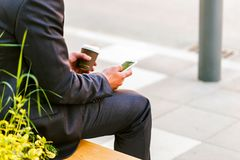 Young Business Man Using Smartphone While Drinks Coffee To Go. And Sitting On Bench Stock Photography