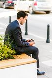 Young Business Man Using Smartphone While Drinks Coffee To Go. And Sitting On Bench Stock Photos