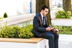 Young Business Man Using Smartphone While Drinks Coffee To Go. And Sitting On Bench Royalty Free Stock Photos