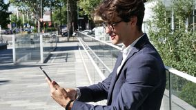 Young business man using tablet computer outdoor. Handsome eleganty young business man wearing jacket sitting and doing working, looking down at a tablet stock video footage