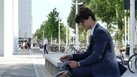Young business man using tablet computer outdoor. Handsome eleganty young business man wearing jacket sitting and doing working, looking down at a tablet stock video