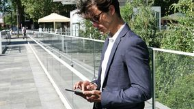 Young business man using tablet PC outdoor. Handsome eleganty young business man wearing jacket standing and using tablet computer, looking down at it, outdoor stock footage
